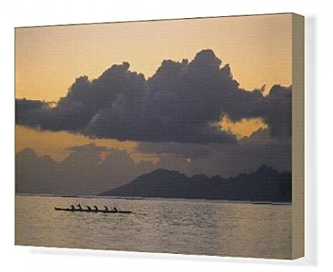 Canvas Print of An outrigger canoe team practices off the coast of the island of Tahiti as the