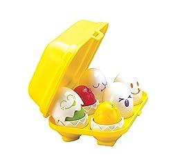 TOMY Versteck- und Quieck Eier. Wer die Eier zerbricht, findet darin bunte Küken, die piepen, wenn man sie drückt. Das Einpacken der Eier wird zum Formensortierspiel, denn jedes Ei hat eine anders geformte Unterseite. Für Kleinkinder ab 12 Monate.