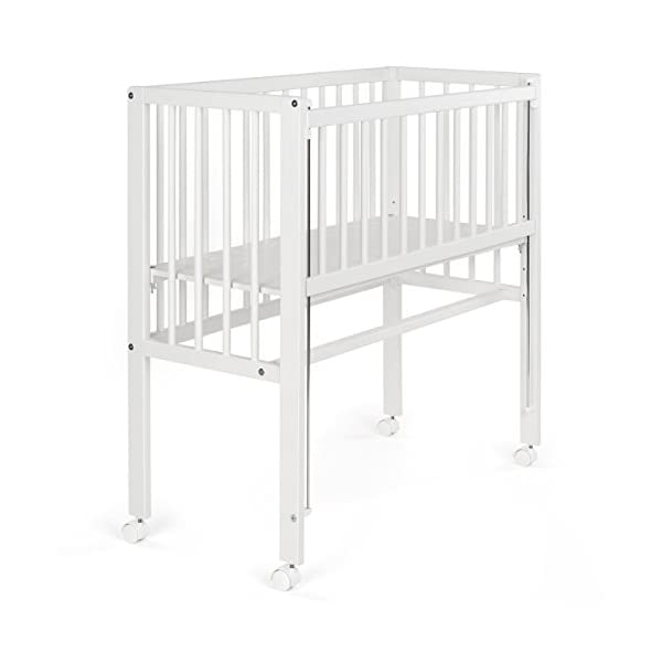 Fillikid Convertible Bedside Crib Vario 2in1 - Height Adjustable Bedside Cot with Wheels | 90 x 40 cm | Solid Beech Wood | Drop Side Rail | Fits Boxspring Beds - White  BEDSIDE CRIB DURING THE NIGHT: The bedside cot enables an easy access, hassle-free night time feeding and allows you to reach your baby without having to get up in the middle of the night. BASSINET DURING THE DAY: Simply pull up the side rail and use the cot as a stand-alone bed or bassinet. Four lockable wheels make it easy for you to move from one room to another having your newborn always on your side. FITS STANDARD AND BOXSPRING BEDS: The bed base can be placed on 4 different heights. It fits on every parent's mattress with a minimum height of 52 cm and a maximum height of 70 cm. The Vario Bedside Crib can easily be attached to your bed with the included support strap. 3