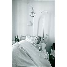 Vintage fotográfico de un hombre tumbado en la cama en un hospital.