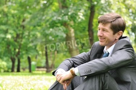 """Leinwand-Bild 140 x 90 cm: """"Senior people series - smiling mature business man siting on green grass and relaxing in park"""", Bild auf Leinwand"""