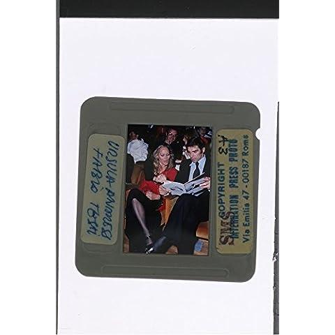 Slides photo of Ursula Andress and Fabio Testi reading at something.