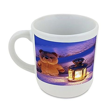 Mug with Teddy bear and a lit lantern near a snow covered fence