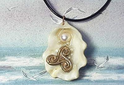 Pendentif .Triskel celte fait main en bronze couleur perles d'eau douce et coquille d'huitre blanche Sur lien de cuir noir