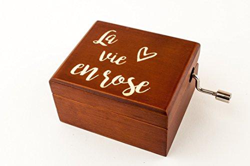"""Pequeña caja musical de madera grabada con la frase """"La vie en rose"""" junto con un corazón. Está lacada en color de madera envejecida y en su interior contiene un espejo (en la parte interior de la tapa) y el mecanismo musical con la melodía de La vie..."""