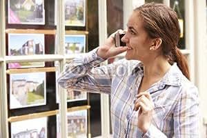 "Leinwand-Bild 50 x 30 cm: ""Happy Young Woman On Phone Outside Estate Agents"", Bild auf Leinwand"