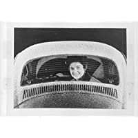 Vintage foto di donna seduta al sedile posteriore di un Volkswagen Beetle auto.