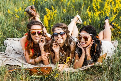 Wunschmotiv: Three cute hippie girl lying on the grass among the wildflowers, best friends having fun and laughing, accessories sunglasses, feathers in their hair, bracelets, flash tattoo, indie Bohemia boho style #118576090 - Bild als Foto-Poster - 3:2 - 60 x 40 cm / 40 x 60 cm (Girl Cute Hippie)