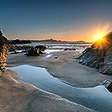 Wallario Glasbild Sonnenuntergang hinter einem Felsen am Strand - 50 x 50 cm in Premium-Qualität: Brillante Farben, freischwebende Optik