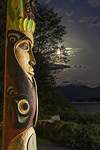 Kevin Smith / Design Pics – A large totem pole lit up at night in Sitka National Historic Park with the moon and clouds in the background; Sitka Alaska United States of America Photo Print (60.96 x 96.52 cm)