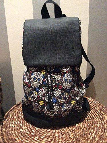 Mochila hecha a mano de polipiel negro tanto en la solapa como en la base y tela de con motivos calaberas.