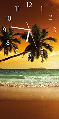 Wallario Design Wanduhr Palmen am Sandstrand bei untergehender Sonne aus Acrylglas, Größe 30 x 60 cm
