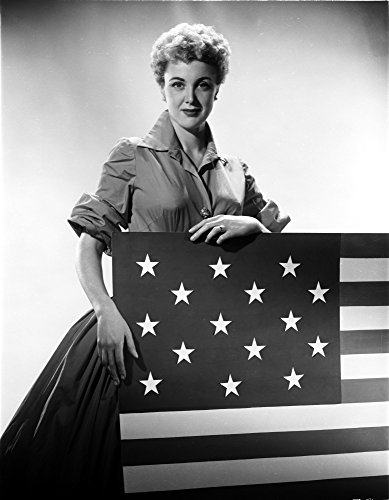The Poster Corp Jan Sterling Posed in Velvet Shirt and Pleated Skirt with Rolled Up Sleeves While Holding a Flag Photo Print (60,96 x 76,20 cm) - Sleeve Flag Shirt