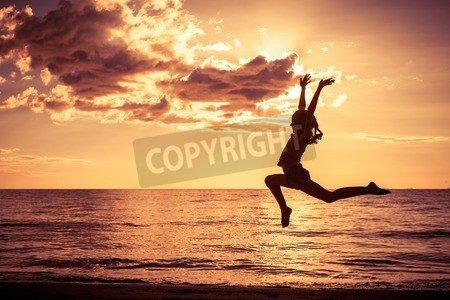 "Leinwand-Bild 50 x 30 cm: ""Happy girl jumping on the beach at the sunset time"", Bild auf Leinwand"