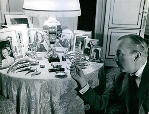 vintage-photo-of-a-photo-of-antonio-castillo-holding-a-cigarette-while-looking-at-the-portrait-of-a-