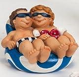 Fröhliches Urlauberpaar auf einer Luftmatratze als Dekofigur