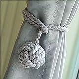 Un par de abrazaderas de cortinas artesanales con diseño de una bola de nudos al final del cordón.