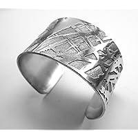 Bracciale rigido e aperto, tipo cuff, in alluminio inciso chimicamente e forgiato a mano, con finitura lucida e testo personalizzato.