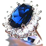 Free Engraving of your choice! Stunning Royal Blue World Class Lab Diamonds Ring. Elegant Sapphire 14.1mm Centre Stone Surrounded by Flawless Rounds. 5.9gr Weight. Rhodium Electroplated.