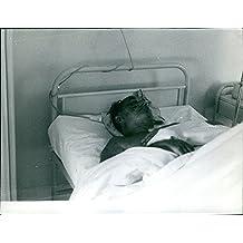 Vintage Foto de Jack Warner tumbado sobre un cama de hospital.