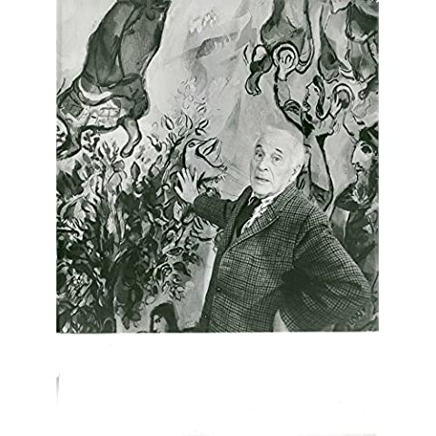 Marc Zakharovich Chagall standing in front of a painting.