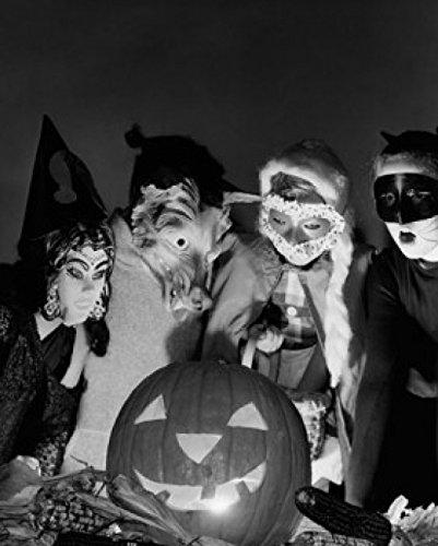 Four Children Wearing Halloween Costumes Looking at an Illuminated Jack o' Lantern Poster Drucken (60,96 x 91,44 cm)