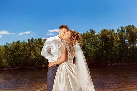 Poster-Bild 80 x 50 cm: 'Young happy wedding couple is kissing outdoors at honeymoon sea vacation.',...