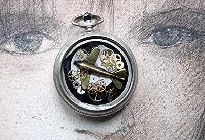 Pendentif unisexe steampunk, boitier de montre gousset recyclé, 1 cadran et des rouages de montre, petit avion couleur bronze, de la résine cristal.