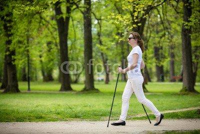 druck-shop24 Wunschmotiv: Nordic walking - middle-age woman working out in city park #123208900 - Bild auf Forex-Platte - 3:2-60 x 40 cm/40 x 60 cm