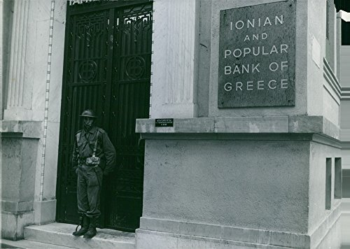 vintage-photo-of-a-guard-standing-at-the-entrance-gate-of-a-building-with-a-sign-on-the-wall-written