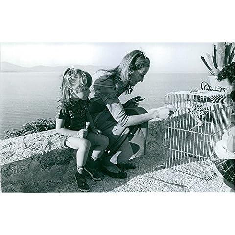 Vintage Foto de un pájaro en una jaula; De Alimentación De Eva Renzi sentado junto a su es su hija.