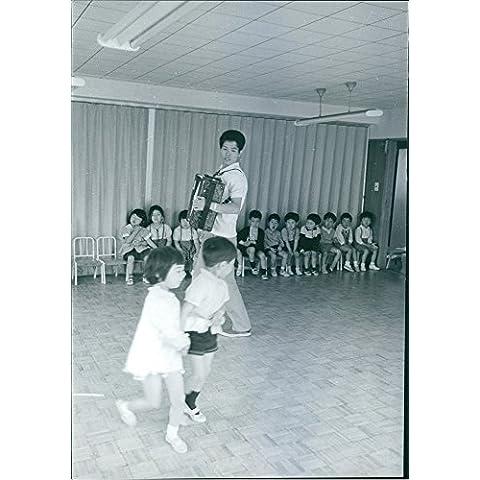 Vintage fotográfico de un hombre tocando acordeón con dos niños en la pista de baile mientras los otros niños está sentado detrás.