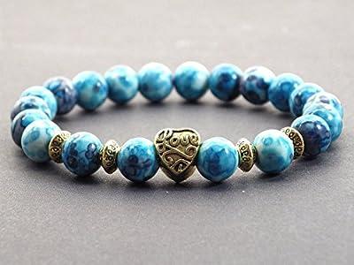 Bracelet en perle de jade blanc teintées en bleu avec perle dorée en forme de coeur.