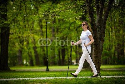 druck-shop24 Wunschmotiv: Nordic walking - middle-age woman working out in city park #116150705 - Bild hinter Acrylglas - 3:2-60 x 40 cm/40 x 60 cm