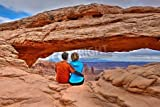 Poster-Bild 90 x 60 cm:Young adults sitting and hugging by arch. Mesa Arch in Canyonlands National Park. Moab. Cedar City. Utah. United States., Bild auf Poster