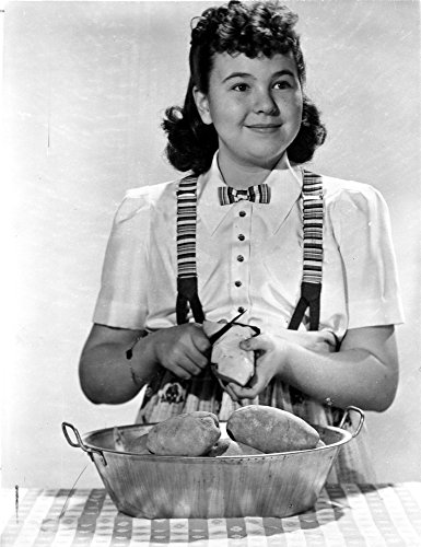The Poster Corp Jane Withers Posed in White Short Sleeve Bodice and Jumper Skirt with Hands Peeling a Potato Photo Print (60,96 x 76,20 cm) -
