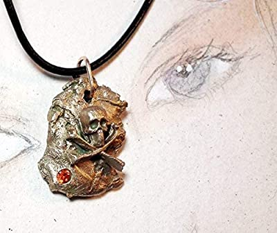 Pendentif, bijou unisexe, Météorite avec crane de pirate aux fémurs croisés faite main en bronze couleur or et un C.Zirconia rouge Sur lien de cuir noir. Pièce unique, pour hommes et femmes