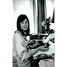Reprint of Françoise Hardy typing and looking at camera.