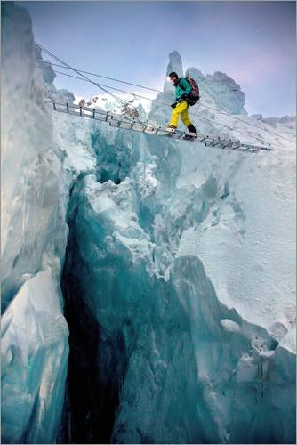 Stampa su tela 80 x 120 cm: An expedition member steps across a bridge of aluminum ladders lashed together above a crevasse in t di Andy Bardon / National Geographic - poster pronti, foto su telaio...