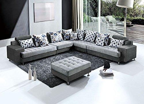 grande divano ad angolo a 2 colori, grigio chiaro e grigio scuro con cuscini a fantasia e pouf centrale.