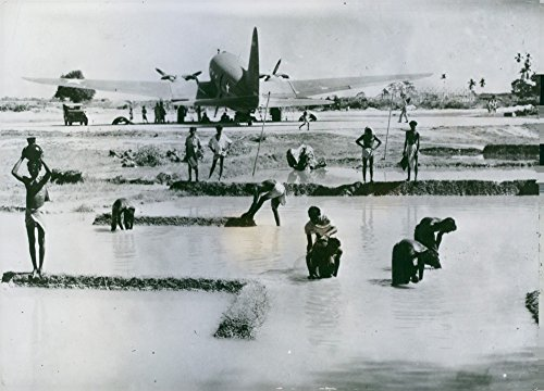vintage-photo-of-us-air-transport-base-in-india-some-workers-are-bathing-in-the-pool-beside-the-runw
