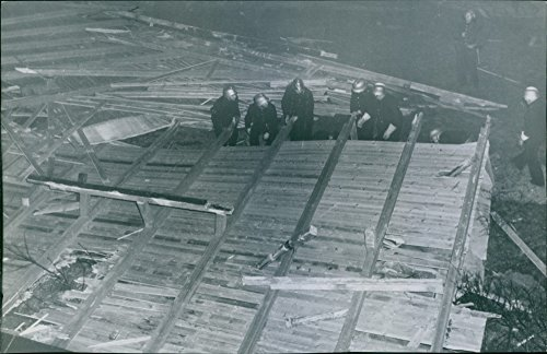 vintage-photo-of-the-entire-roof-with-sheet-metal-planks-and-rafters-ended-up-upside-down-on-the-far