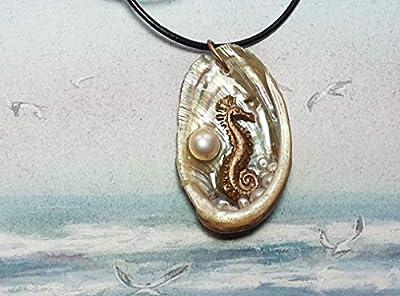Pendentif, hippocampe fait main en bronze couleur or, perle d'eau douce cabochon blanche, sur une coquille dormeau.abalone lacet de cuir