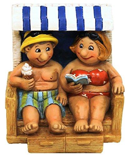 Fröhliches Urlauberpaar im Strandkorb mit Eis und Buch