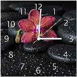 Wallario Glas-Uhr Echtglas Wanduhr Motivuhr • in Premium-Qualität • Größe: 30x30cm • Motiv: Orchideen-Blüte auf schwarzen Steinen, benetzt mit Wasser-Tropfen