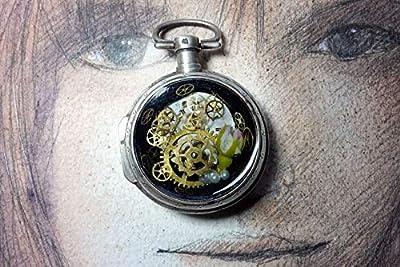 Pendentif romantique unisexe steampunk fait d'un boitier de montre vintage recyclé en laiton argenté contenant un cadran, des rouages, un bouton de rose dans de la résine cristal. Lien de cuir noir