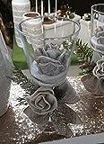 Composizione natalizia formata da un vasetto in vetro con base a bicchiere che contiene una candela in cera argentata a forma di rosa,e piccola composizione di fiocco e rosa in tessuto sul gambo del bicchiere - addobbi natalizi,arredo,pensiero per natale
