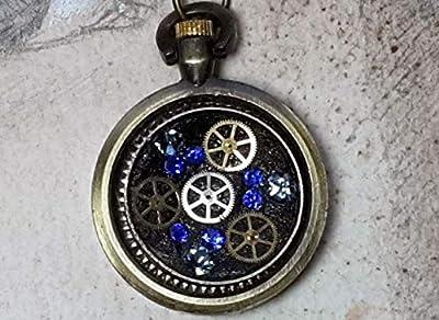 Pendentif steampunk, petit boitier de montre gousset couleuur bronze et rouages de montre mécanique, cabochons de cristal swarovski bleus, résine noire- chaine pour homme et femme