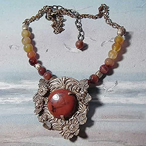 Necklace made of a goldy bronze center piece , decorated with a beautiful round red Jasper cab and hanging on a row of natural agat and bronze beads and and finished with a pretty vintage