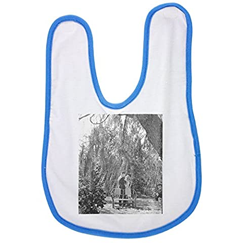 Blue baby bib with Man and woman are about to kiss underneath tree. people, man, woman, garden, chairs, standing, kiss, relationship, romance, love, heteroseksual couple, tree,